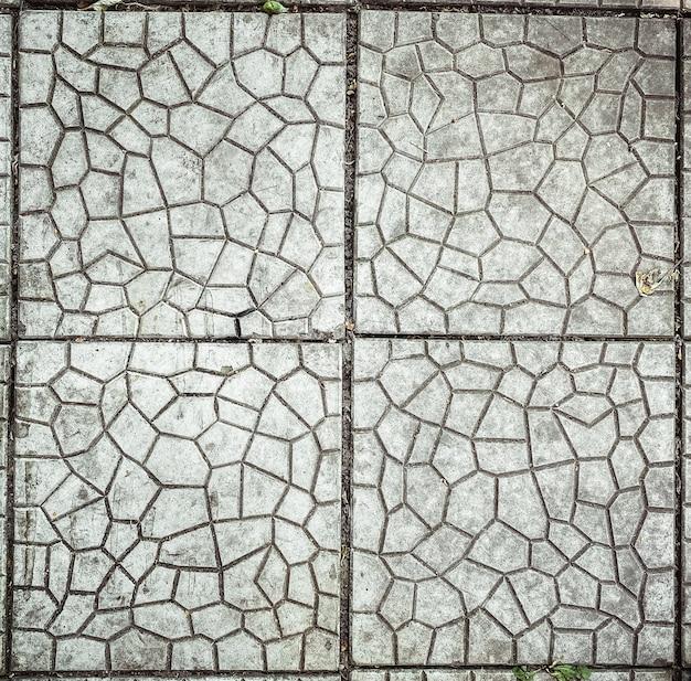 Primo piano quadrato sulla struttura del pavimento piastrellato all'aperto di pietra grigia