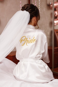 Primo piano ritratto di elegante sposa in abito bianco con velo lungo con la scritta