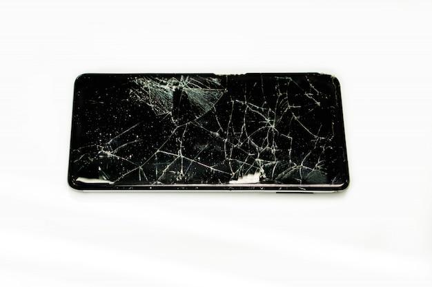 Primo piano rotto e tirato giù dell'isolato nero del telefono cellulare su fondo bianco.