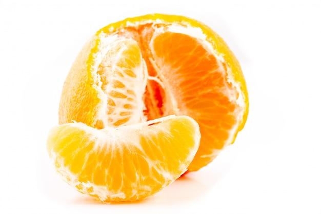 Primo piano sbucciato della fetta del mandarino isolato su un bianco