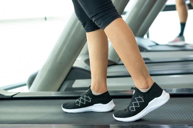Primo piano scarpe da ginnastica ragazza fitness in esecuzione sul tapis roulant su pista, donna con gambe muscolose in palestra