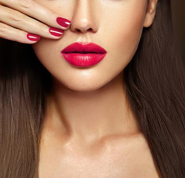 Primo piano sexy rosa delle unghie e delle labbra. bocca aperta. manicure e trucco.
