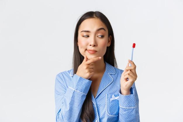 Primo piano sparato di curiosa bella ragazza asiatica in pigiama blu, guardando premuroso allo spazzolino da denti, avendo un'idea interessante, pensando in bagno durante la routine igienica mattutina, muro bianco