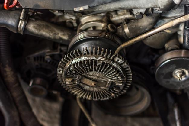 Primo piano sporco del motore dell'automobile smontata alle componenti del motore al garage dell'automobile