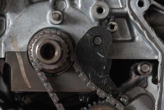 Primo piano sporco del motore dell'automobile smontata alle parti e agli ingranaggi del motore al garage dell'automobile