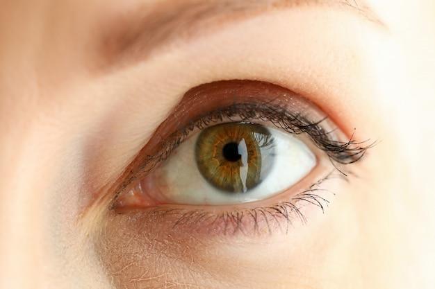 Primo piano stupefacente dell'occhio colorato verde arancio sinistro femminile