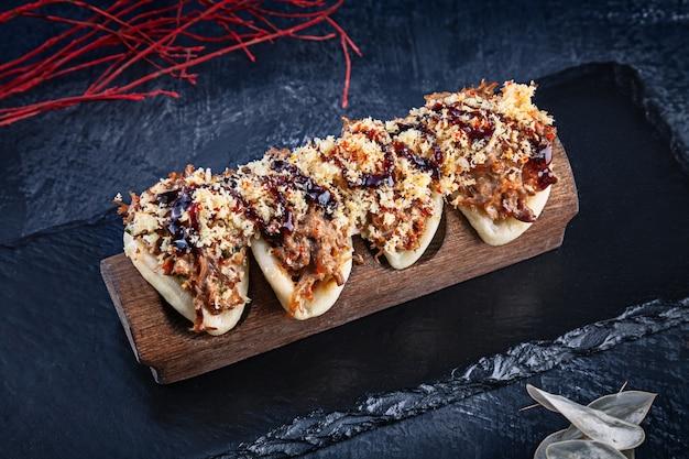 Primo piano su gua bao, panini al vapore con carne (anatra). bao è servito con gustose guarnizioni su sfondo scuro. cucina asiatica. bao gua al vapore panino asiatico. fast food in stile giapponese