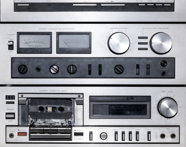 Primo piano su quadranti e controlli di un lettore musicale stereo vintage che mostra il registratore per vecchie cassette audio