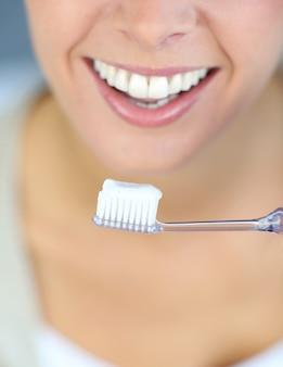 Primo piano sul sorriso toothy della donna che pulisce i suoi denti