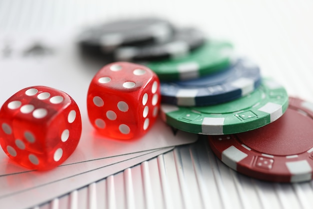 Primo piano sul tavolo ci sono carte da gioco con chip di dadi