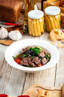 Primo piano sulla carne di manzo arrosto con verdure in una ciotola bianca sul tavolo di legno