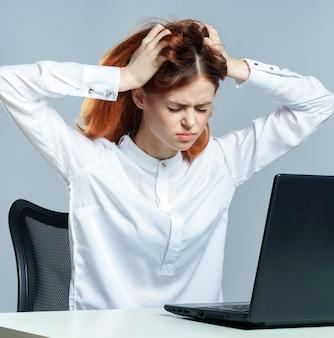 Primo piano sulla donna con mal di testa che lavora al computer portatile
