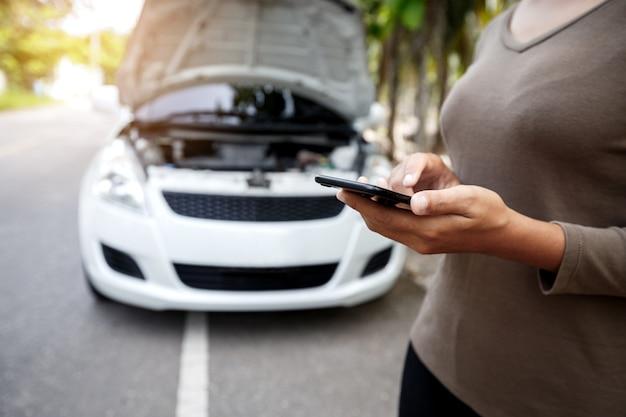 Primo piano sulla mano della donna utilizzando il servizio di emergenza auto chiamata di telefono
