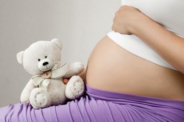Primo piano sulla pancia incinta. la donna aspetta un bambino con un tenero orsacchiotto che le raggiunge il ventre.