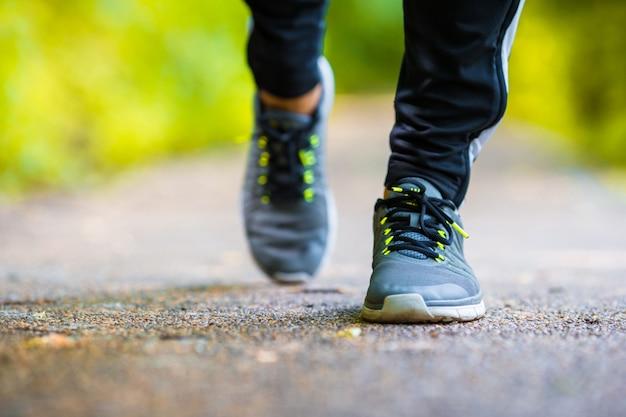 Primo piano sulla scarpa dei piedi dell'uomo del corridore dell'atleta che corrono sulla strada