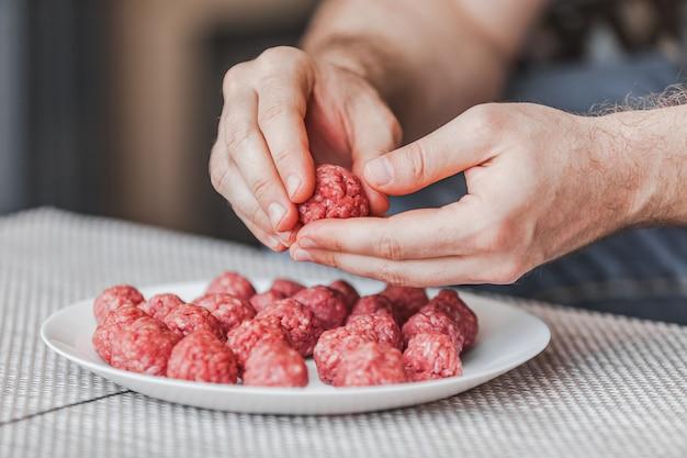 Primo piano sulle mani che preparano le polpette con carne tritata cruda