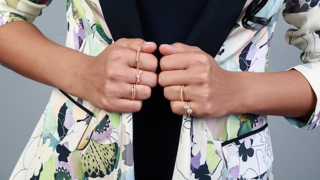 Primo piano sulle mani di ragazze che indossano anelli dorati e che tengono giacca con motivo floreale