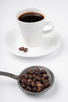 Primo piano tazza di caffè con fagioli arrostiti