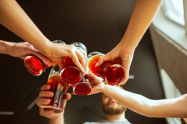 Primo piano tintinnio. giovane gruppo di amici che bevono birra, divertirsi, ridere e festeggiare insieme.