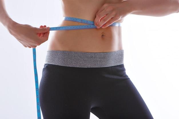 Primo piano tonico dello stomaco su una priorità bassa bianca.