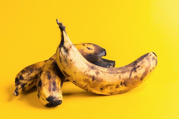 Primo piano tre banane brutte annerite troppo mature su fondo giallo.