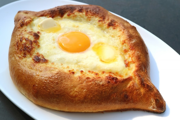 Primo piano un piatto di adjarian khachapuri, formaggio e pane georgiano tradizionale pieno di uova