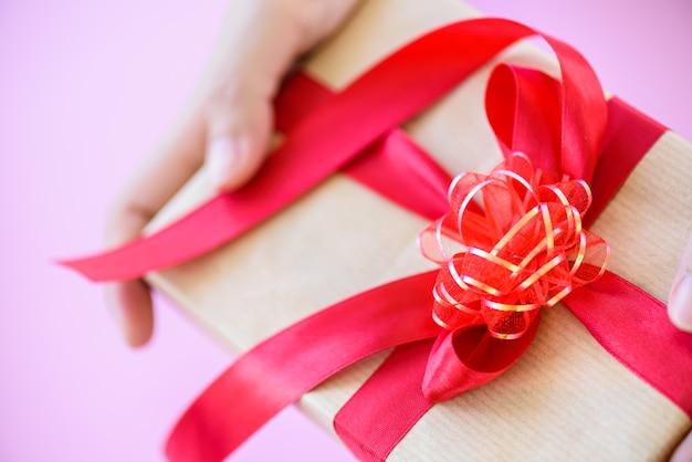 Primo piano un regalo con nastro rosso. vacanze, regali, natale