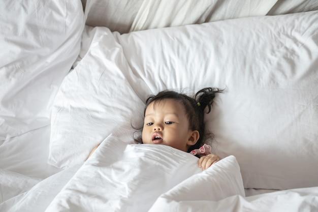 Primo piano una bugia della bambina sul letto sotto la coperta di mattina
