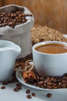 Primo piano una tazza di caffè con chicchi di caffè in un sacco e piattino, latte, cannella secca su sottopentola e superficie bianca. verticale