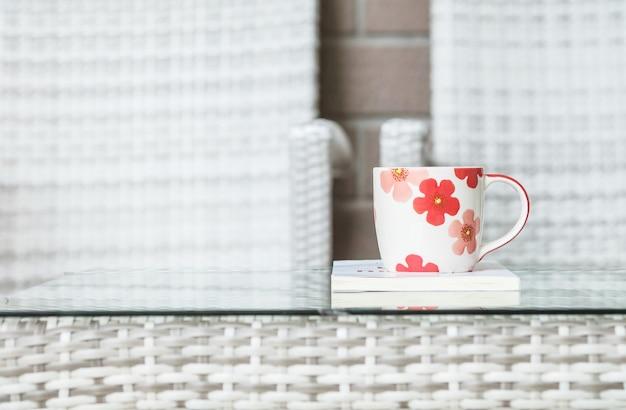 Primo piano una tazza di caffè sul libro bianco sullo scrittorio di legno