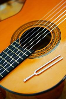 Primo piano verticale dell'angolo alto delle corde di una chitarra classica
