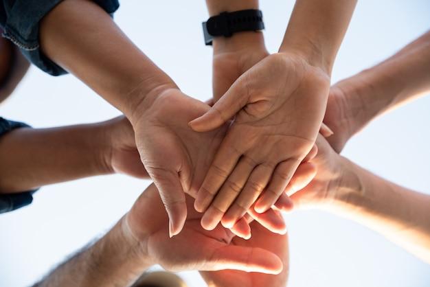 Primo piano vista dal basso di persone che uniscono le loro mani.