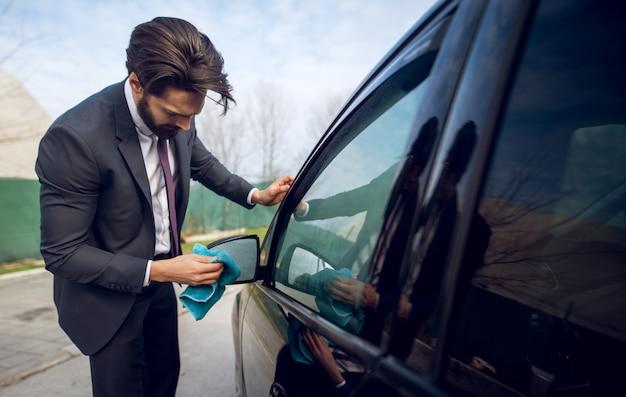 Primo piano vista della moda giovane concentrato lavoratore laborioso pulizia specchietto retrovisore della sua auto nera con un panno in microfibra blu.