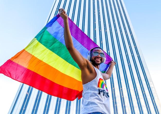 Primo piano vista di un uomo omosessuale nero che è felice con una bandiera arcobaleno di un orgoglio gay in strada