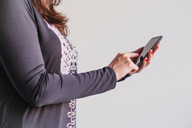 Primo piano vista di una giovane donna con il cellulare. indossa un costume scheletro bianco e nero. concetto di halloween. ambientazione interna. tecnologia