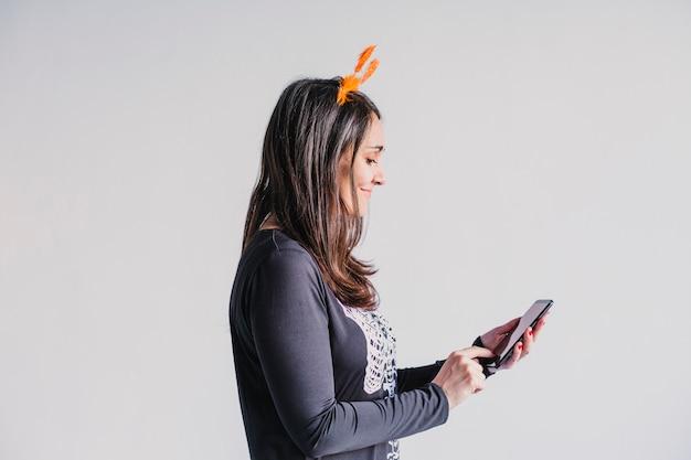 Primo piano vista di una giovane donna con il cellulare. indossa un costume scheletro bianco e nero. concetto di halloween. tecnologia