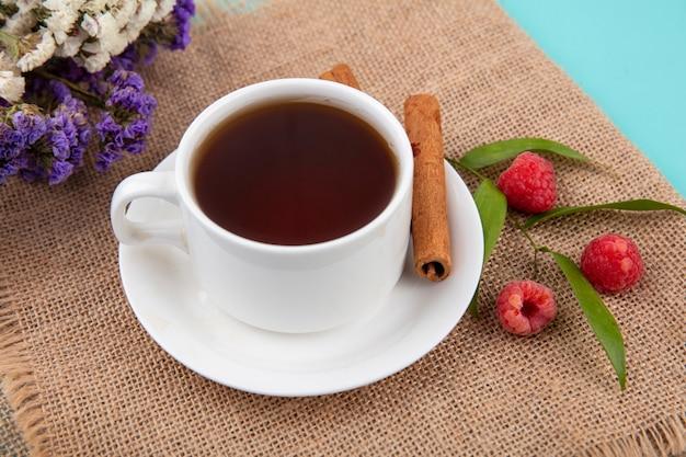 Primo piano vista di una tazza di tè e cannella sul piattino con lamponi e foglie e fiori su tela di sacco