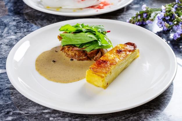 Primo piano vista su gratin di patate in stile perfetto con salsa verde e filetto di tacchino grigliato con spinaci