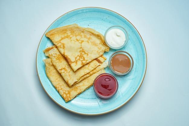 Primo piano vista su gustose crepes francesi giallo e rosso marmellata, panna acida in un piatto di ceramica su grigio. gustosi pancake ucraini