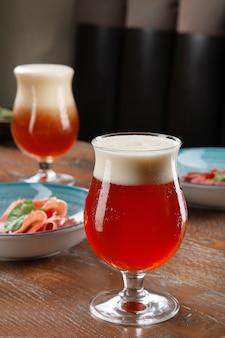 Primo piano vista sulla birra ambrata fredda in un bicchiere con spuntino al bar sul tavolo