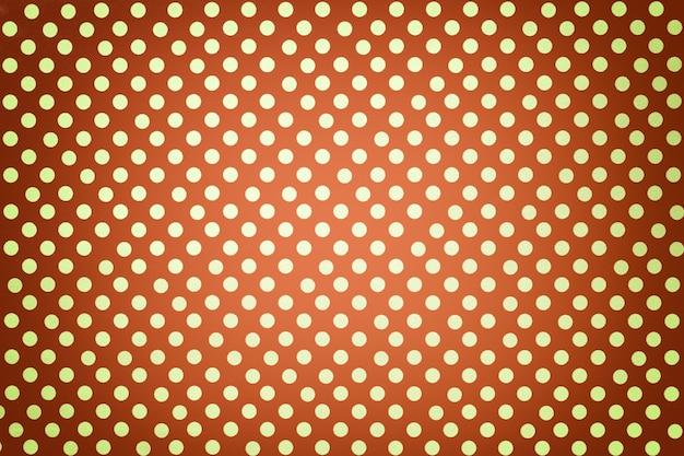 Priorità bassa arancione-chiaro da carta da imballaggio con un reticolo del primo piano dorato del puntino di polka.