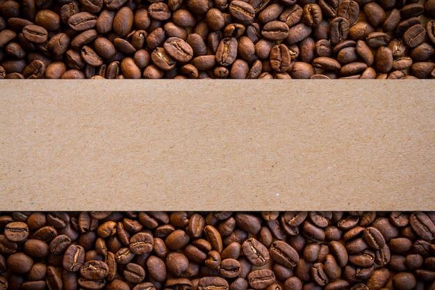 Priorità bassa arrostita dei chicchi di caffè con l'etichetta in bianco della carta marrone