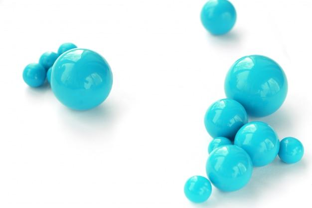 Priorità bassa astratta dei branelli blu di plastica delle dimensioni differenti su una priorità bassa bianca