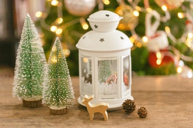 Priorità bassa del bokeh di natale con la lanterna bianca, la renna di bagattella di legno, le pigne e l'albero di natale.