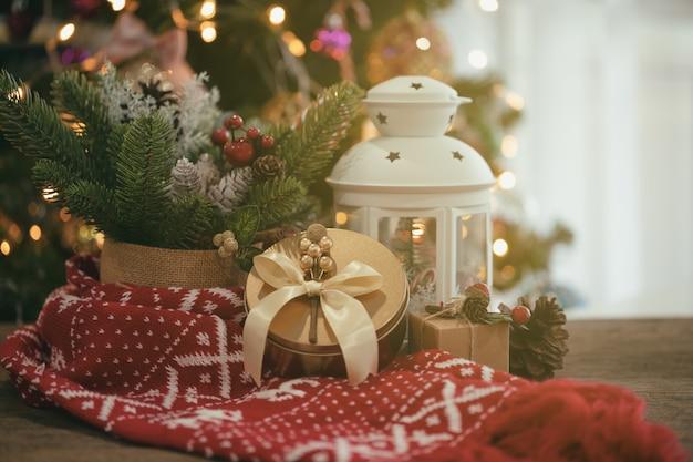 Priorità bassa del bokeh di natale decorata con la sciarpa rossa, il contenitore di regalo, la lanterna bianca, la pigna, albero di natale.