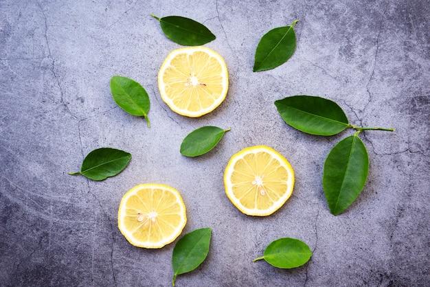 Priorità bassa del limone / fetta senza giunte del limone e foglio verde su oscurità