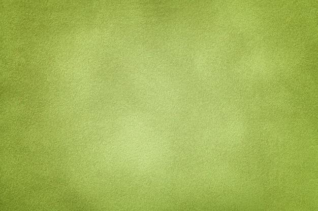 Priorità bassa del primo piano verde chiaro del tessuto della pelle scamosciata.