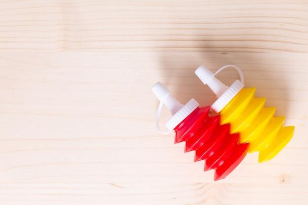 Priorità bassa dell'alimento la salsa ketchup e la senape di pomodoro comprimono le bottiglie su fondo di legno