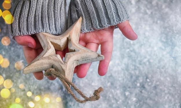 Priorità bassa della neve di inverno, mani dei bambini che tengono l'ornamento di natale