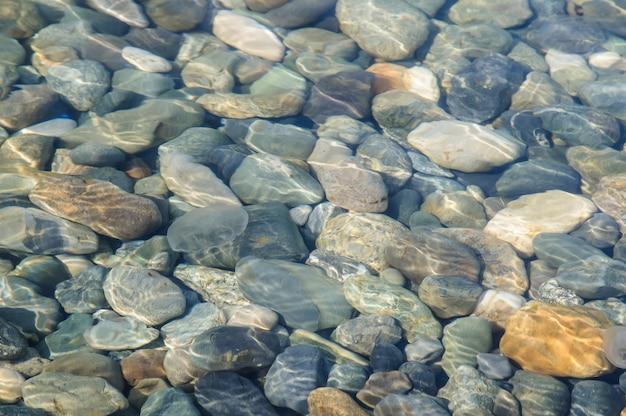 Priorità bassa delle pietre colorate mare sotto acqua.